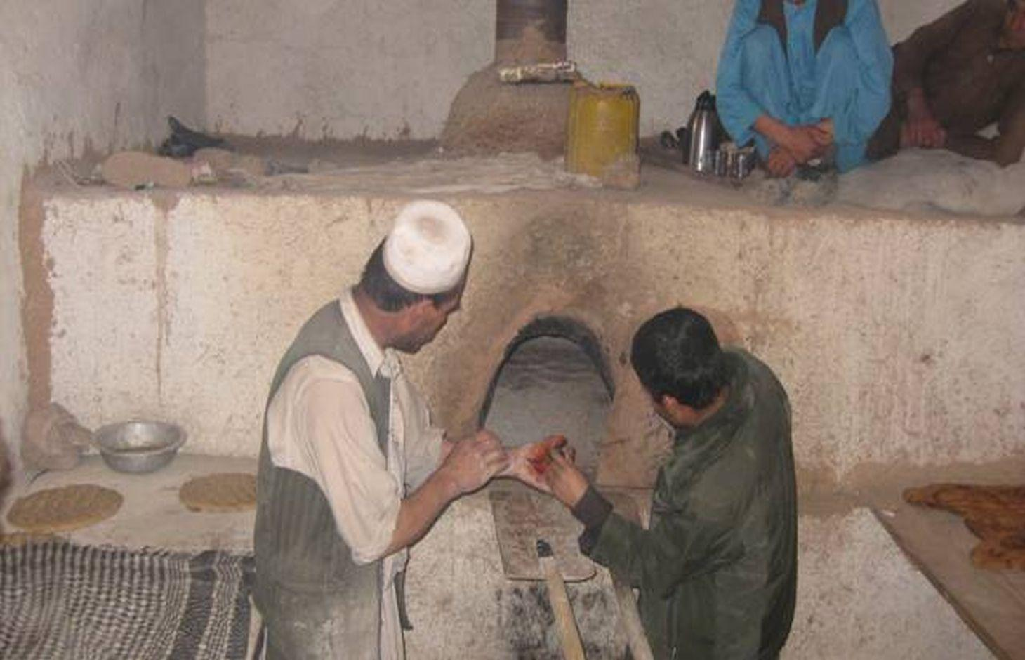 An overview of a community bakery from inside. The bakeries and his assistant are showing the Dash/oven using a torch.