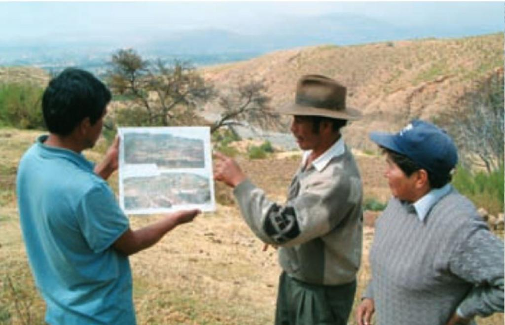 Individual planning (at farmer level) of activities to treat the large gully in the background: a PROMIC engineer and local people are involved. Note the city of Cochabamba in the distance.