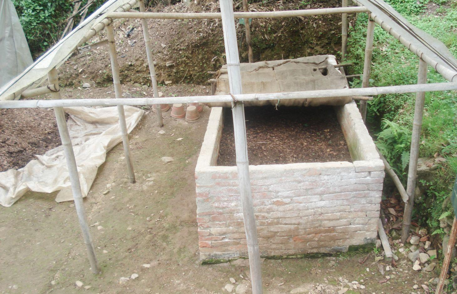 Structure used for vermicomposting showing above ground bin, cover, and shed